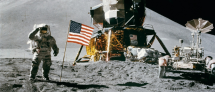 Astronaut standing on the moon next to an American flag and lunar module