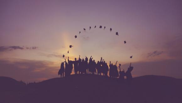 אנשים בשקיעה זורקים את כובעי סיום הלימודים ויוצרים קשת