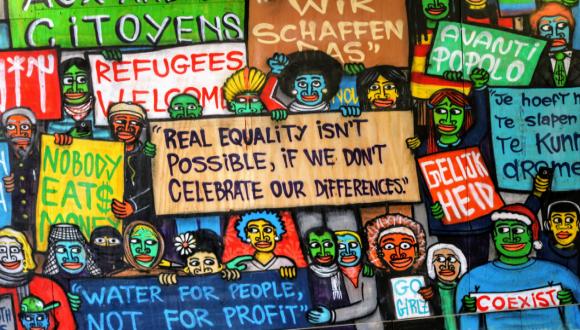 אנשים בצבעים שונים מחזיקים שלטים של סובלנות